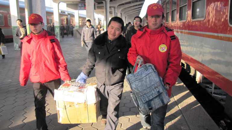 兰州铁路局春运志愿者为旅客搬运行李